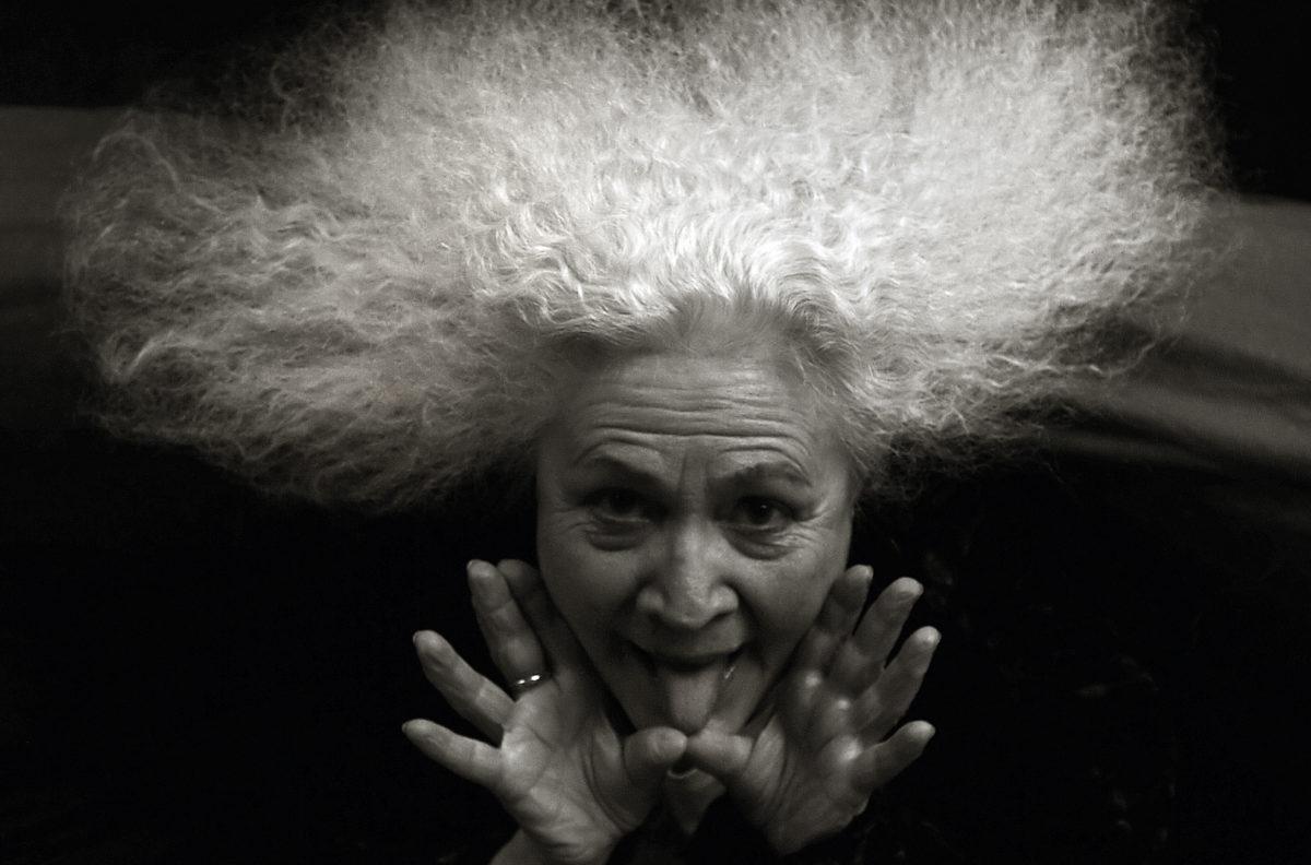 Konstnär Outi Heiskanen, vit hår, tungan ut. Svartvit bild.