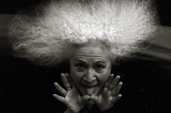 Muotokuva Outi Heiskasesta, henkilö kieli ulkona suusta, valkoinen kihara tukka. Mustavalkoinen kuva.